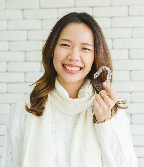 a patient holding their Invisalign trays and smiling