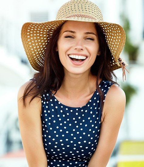 A young female with long, dark hair, wearing a woven hat and polka dot dress and showing off her new smile